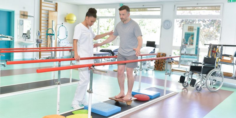 Man balancing with physiotherapist