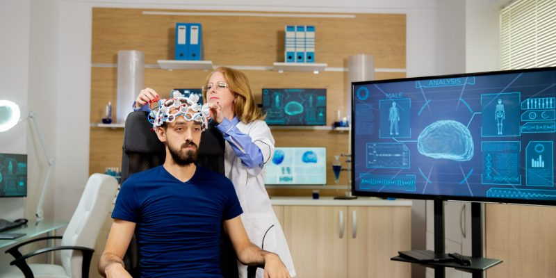 Patient who undergoes a brain scan procedure in a neurological center. Neurology scanning headset